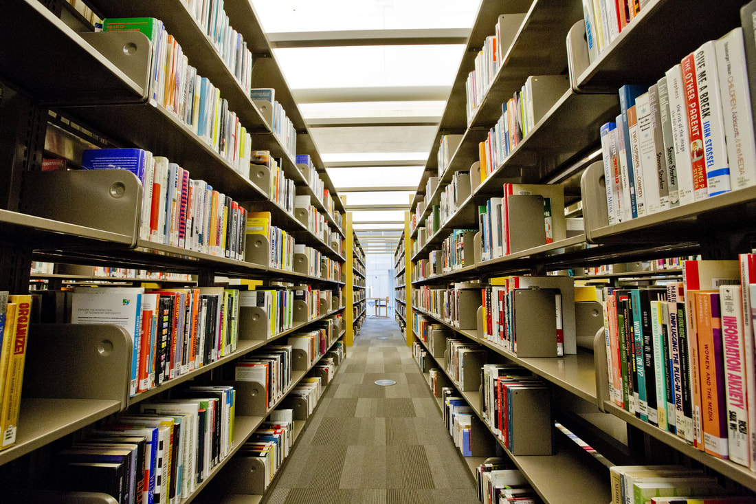 Library shelves leading to bright room